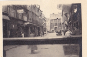 This was taken over the windshield of a jeep. Very narrow European street, buildings appear undamaged. Belgium was liberated by British and Canadian troops.