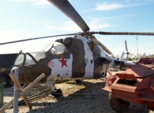 Front view of MI 24 Russian Hind helicopter. Where the museum obtained this monster gunship I do not know. Military hardware from other countries is not common at the museum and as far as I know this is the only piece from the old Soviet Union or the former East Bloc countries. The possible exception is the small red wheeled vehicle parked to the right of the Hind. I do not think it's American and have not been to positively id it as Soviet either.