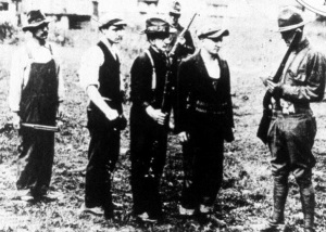Miners surrendering their weapons to the regulars. The man on the far left seems to be carrying a Winchester 73, one of the most common arms used by the miners (for hunting).