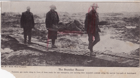 Although badly damaged by some kid's crayon it's still an interesting picture. Gas masks are much in evidence as is the mud! The mud is so bad the stretcher bearers are using a duck board path.
