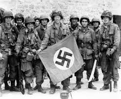 Well known pic of some 101st troopers with a captured Nazi flag.  Even from this picture it can be seen they had a lot to carry.